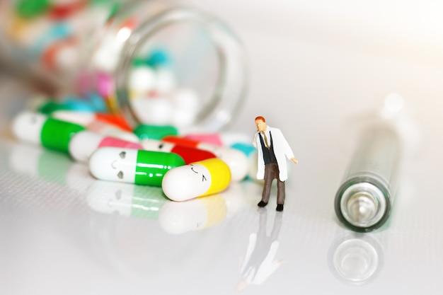 Persone in miniatura: medico con droga e siringa. concetto di assistenza sanitaria.