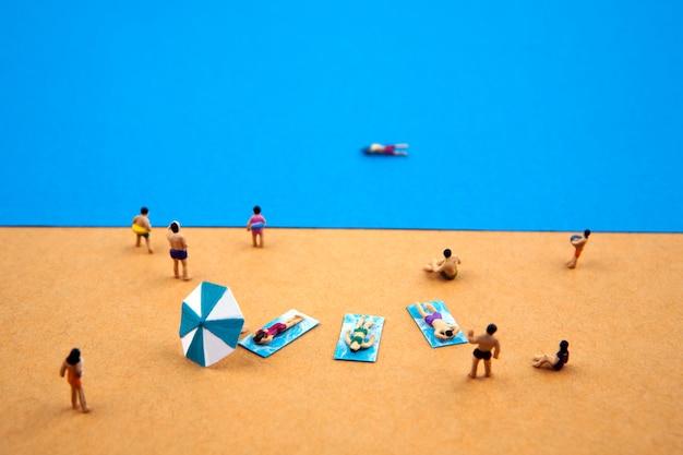 Persone in miniatura nella spiaggia estiva