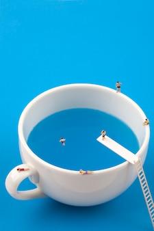 Persone in miniatura nella tazza tazza piscina