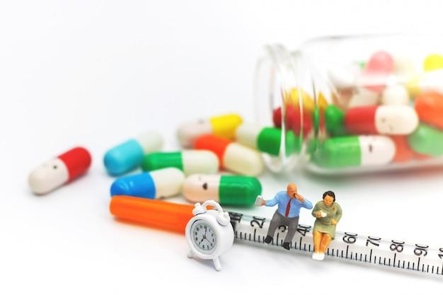 Persone in miniatura, pazienti grassi seduti sulla siringa con farmaci e orologio
