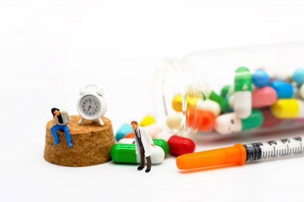 Persone in miniatura: pazienti seduti con farmaci e orologio. concetto di assistenza sanitaria.