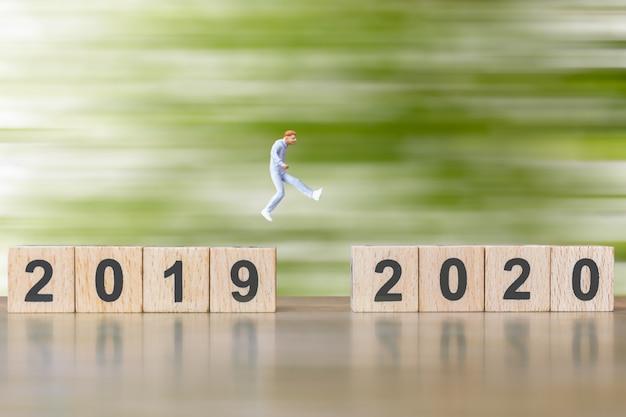 Persone in miniatura salta dal numero 2019 al 2020