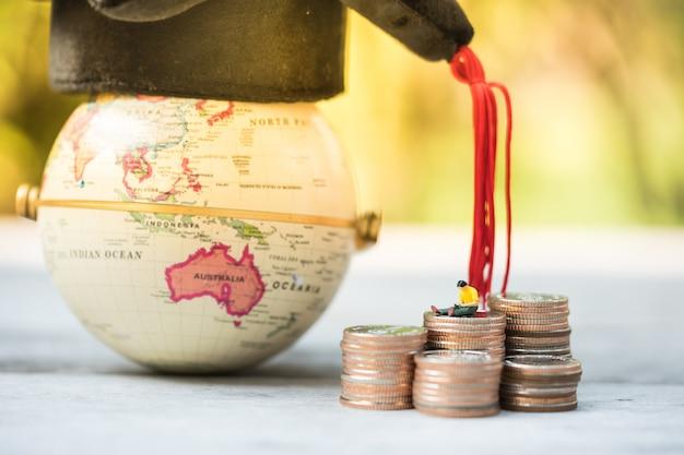 Persone in miniatura seduti e leggendo sulla pila di monete davanti a un globo con cappello di laurea. finanza e istruzione.