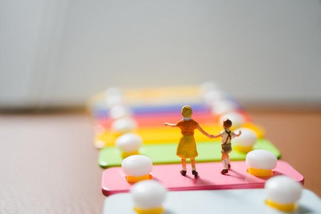 Persone in miniatura, sorella e fratello che camminano sul mini xilofono usando come concetto di famiglia