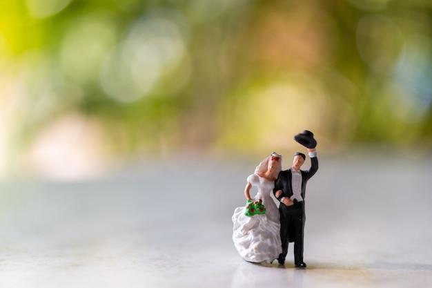 Persone in miniatura: sposi all'aperto con sfondo verde bokeh e copia spazio per il testo