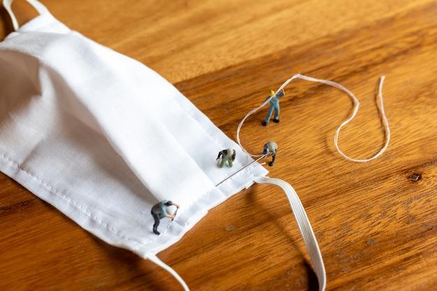 Persone in miniatura: squadra di lavoratori che produce una maschera fatta in casa in tessuto bianco sul tavolo di legno