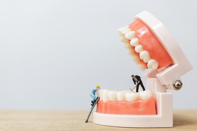 Persone in miniatura: squadra di lavoratori che ripara un dente