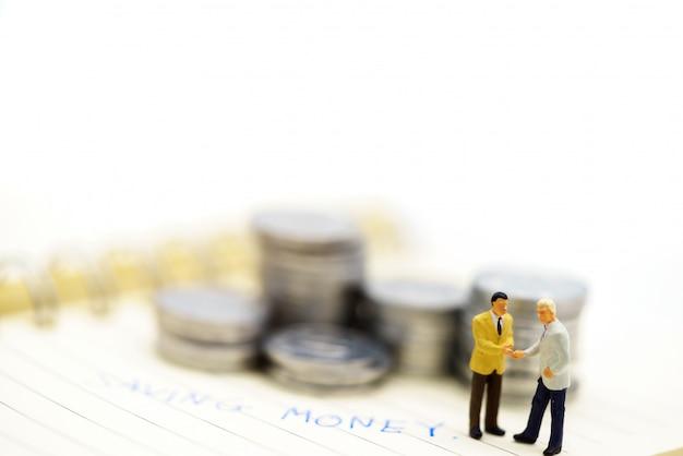 Persone in miniatura: stretta di mano degli uomini d'affari con pila di monete.