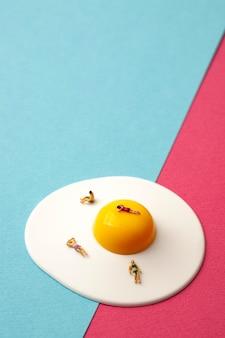 Persone in miniatura su uovo con superficie blu e rosa