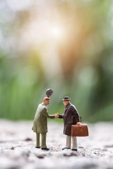 Persone in miniatura: uomini d'affari che si incontrano salutando la stretta di mano scena all'aperto