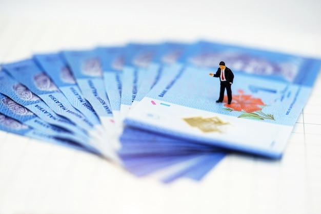 Persone in miniatura uomo d'affari in piedi con i soldi
