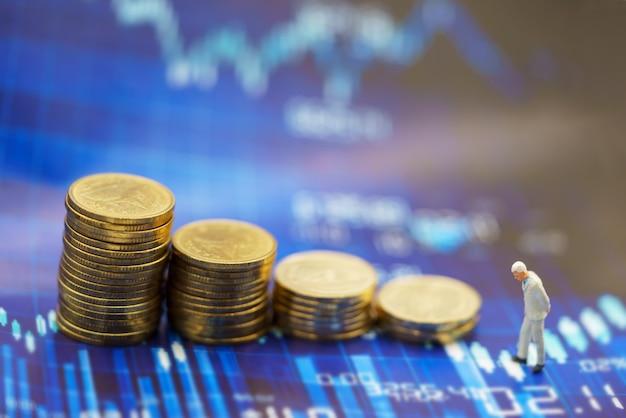 Persone in miniatura uomo d'affari in piedi con la pila di monete