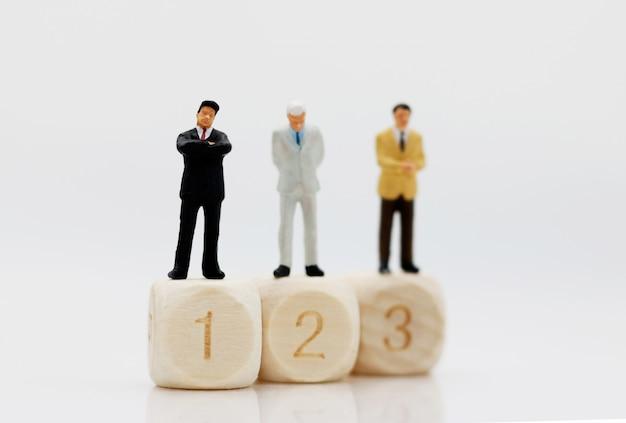 Persone in miniatura: uomo d'affari in piedi sui dadi con il numero 1, 2, 3.