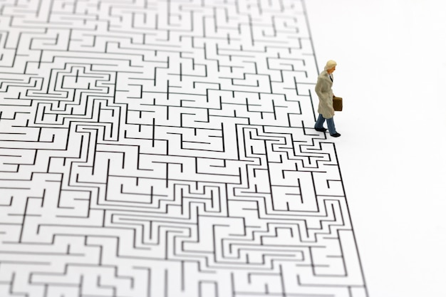 Persone in miniatura: uomo d'affari in piedi sul traguardo del labirinto. concetti di ricerca di una soluzione, risoluzione di problemi e sfida.