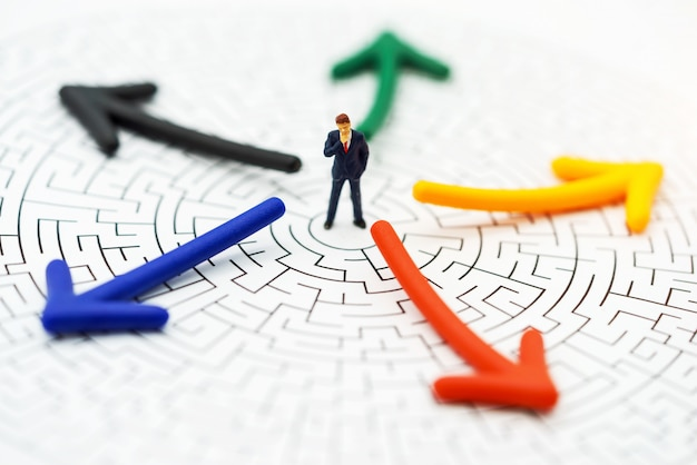 Persone in miniatura, uomo d'affari pensando di rompere il muro in un labirinto