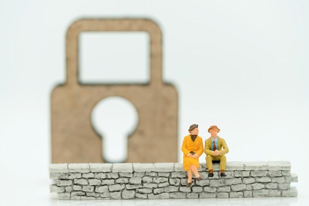 Persone in miniatura: uomo d'affari seduto sul muro con chiave master.