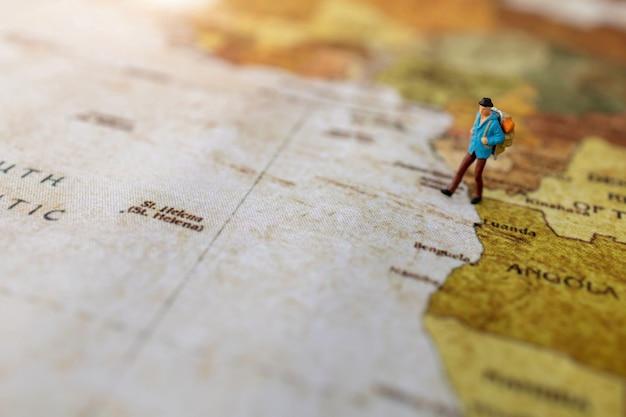 Persone in miniatura: viaggiare con uno zaino in piedi sulla mappa del mondo vintage, viaggi e concetto estivo.