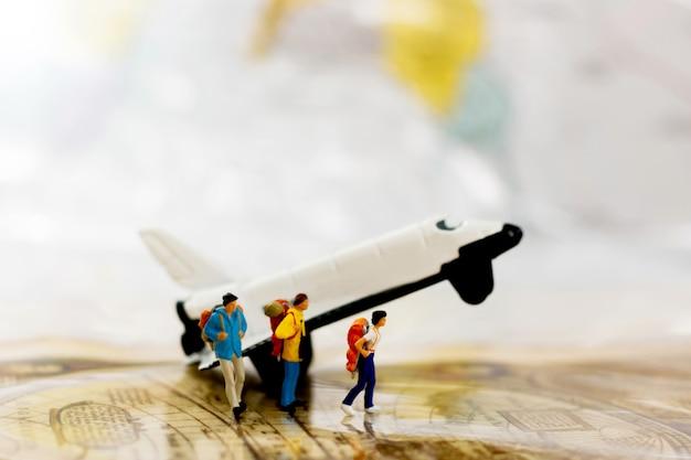 Persone in miniatura: viaggiare con uno zaino viaggiando in aereo.