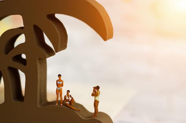 Persone in miniatura: viaggiatore con macchina fotografica in piedi con cocco. concetto di estate.