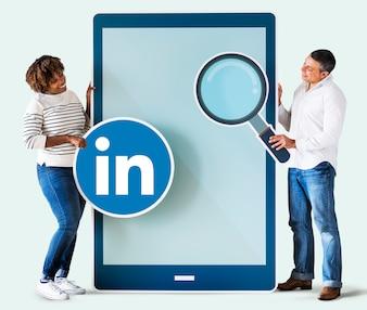 Persone in possesso di un'icona di Linkedin e un tablet