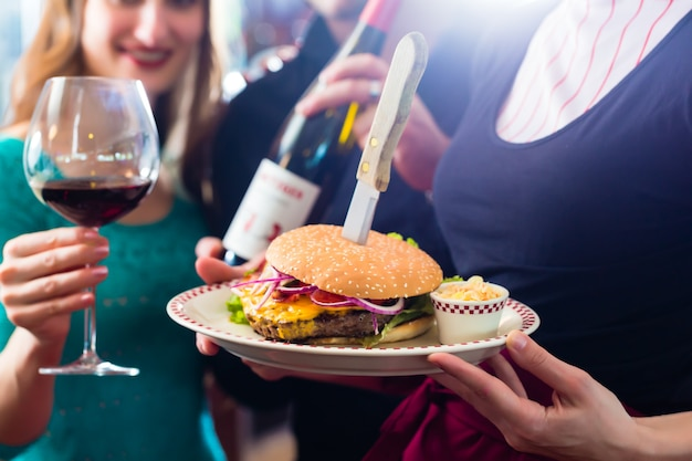 Persone in ristorante americano con hamburger e vino