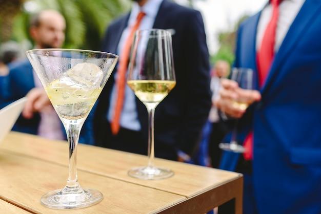 Persone in un cocktail che bevono alcolici dagli occhiali e si divertono alla festa.
