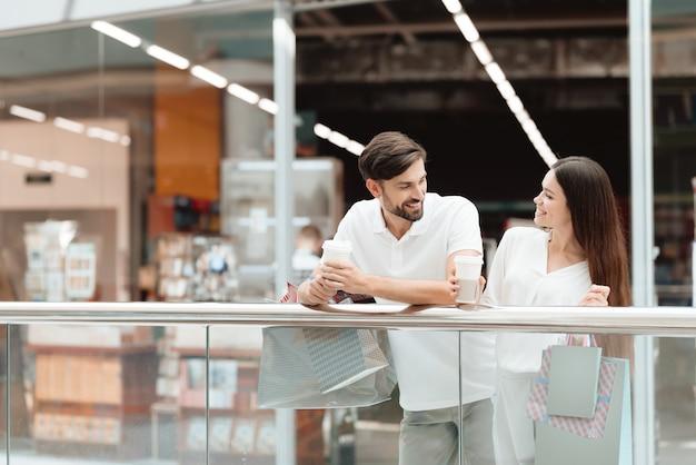 Persone nel centro commerciale. la coppia è felice dopo lo shopping.