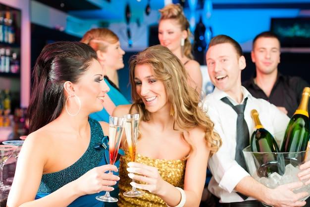 Persone nel club o al bar bevendo champagne
