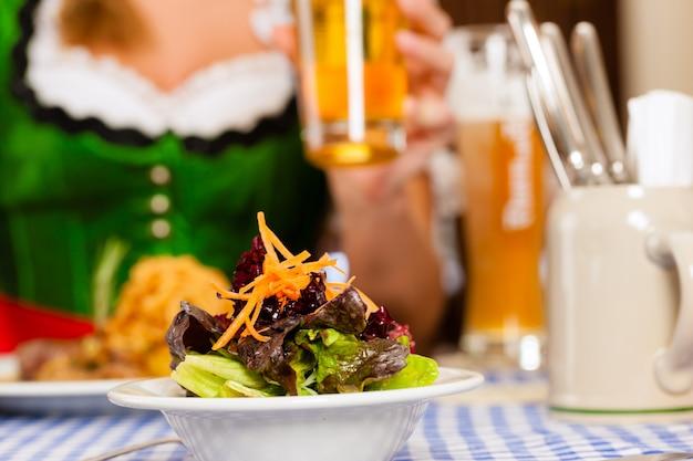 Persone nel tradizionale bavarese tracht mangiare in ristorante o pub