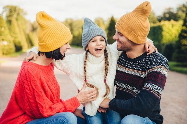 Persone, relazioni e concetto familiare. la bambina sorridente con le trecce abbraccia i suoi genitori