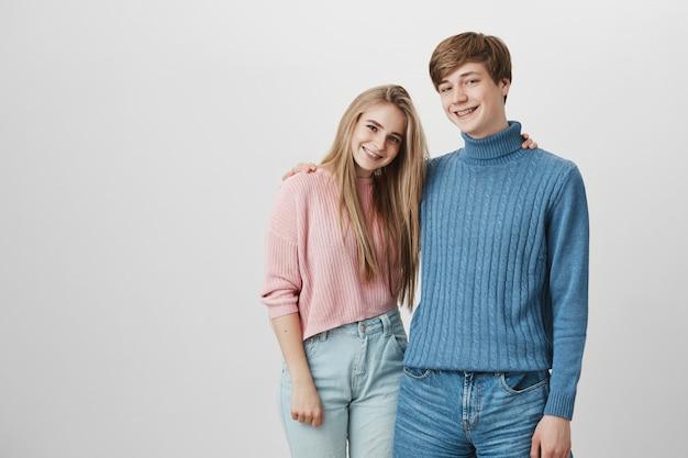 Persone, relazioni, tempo libero e stile di vita. coppia affascinante giovane hipster godendo il tempo libero, guardando felice e gioioso