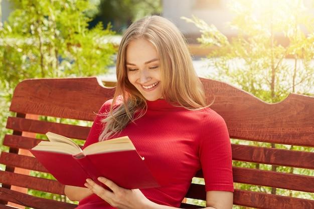 Persone, riposo, hobby, concetto di vacanza. donna bionda allegra in maglione rosso che tiene il suo libro preferito che legge storie divertenti. libro di lettura femminile grazioso al tempo pieno d'ammirazione del banco di legno