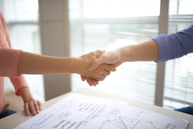 Persone ritagliate si stringono la mano in accordo
