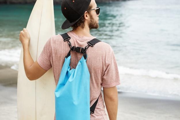 Persone, sport e hobby. snapback d'uso del giovane uomo caucasico ed occhiali da sole alla moda che stanno sulla riva di mare con il surf in sue mani il giorno soleggiato