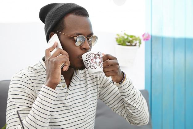 Persone, stile di vita, comunicazione e concetto di tecnologia moderna. giovane studente afroamericano attraente che ha conversazione telefonica mentre bevendo tè o caffè
