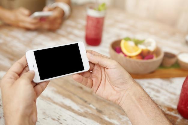 Persone, stile di vita e concetto di tecnologia moderna. chiuda sul colpo delle mani dell'uomo con lo smart phone generico