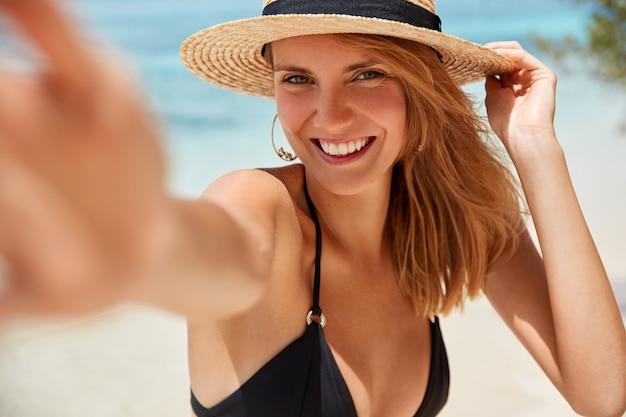 Persone, stile di vita, felicità e concetto di ora legale. bella giovane donna sorridente con espressione allegra posa per fare selfie su sfondo azzurro del mare, felice di avere un buon riposo indimenticabile