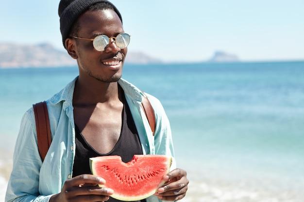 Persone, stile di vita moderno attivo, viaggi, vacanze e concetto di turismo. giovane viaggiatore con zaino e sacco a pelo dalla pelle scura allegro in abbigliamento alla moda che trascorre il giorno di estate soleggiato al mare, godendo dell'anguria succosa
