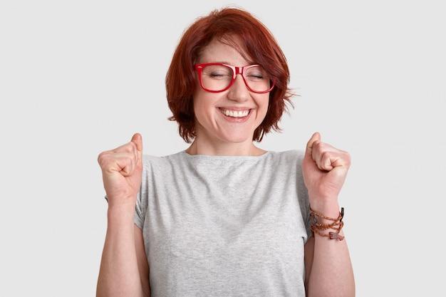 Persone, successo, concetto di celebrazione. felicissima donna dai capelli rossi con i capelli corti, stringe i pugni, ha un sorriso tenero, vestito con indifferenza, modella sulla parete bianca dello studio, esprime emozioni positive
