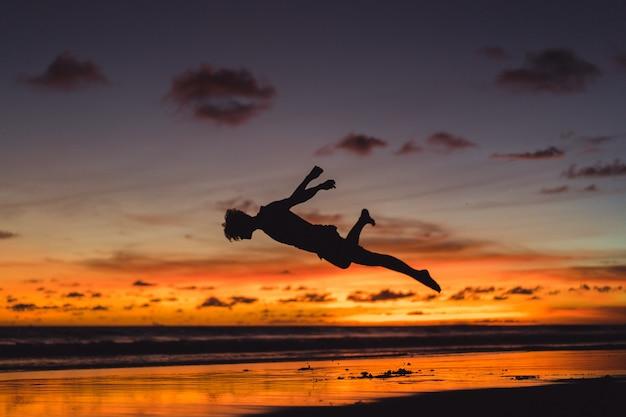 Persone sulla riva dell'oceano al tramonto. l'uomo salta sullo sfondo del sole al tramonto