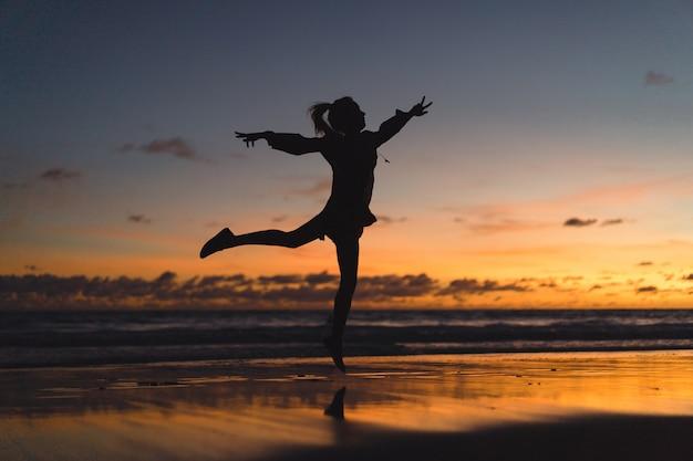 Persone sulla spiaggia al tramonto. la ragazza sta saltando sullo sfondo del tramonto.