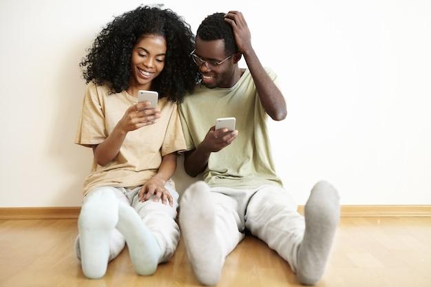 Persone, tecnologia e comunicazione. giovane coppia africana vestita casualmente seduto sul pavimento al chiuso con dispositivi elettronici. ragazza carina navigando sui social media