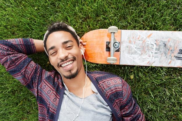 Persone, tempo libero e concetto di stile di vita. il pattinatore gioioso sorridente riposa dopo l'allenamento, si trova sull'erba verde vicino allo skateboard