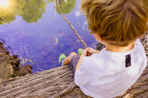 Pesca del ragazzo che si siede su un ceppo al bordo di un fiume.