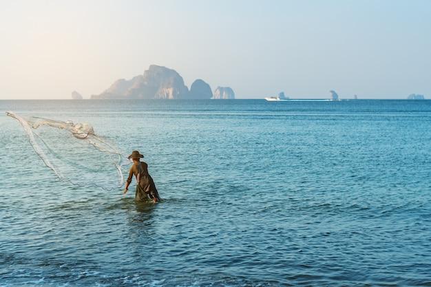 Pesca dell'uomo di fisher nella campagna della spiaggia del mare