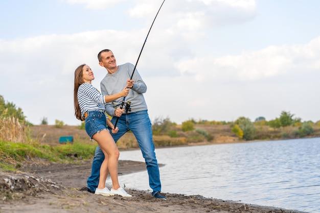 Pesca felice delle giovani coppie dalla riva del lago