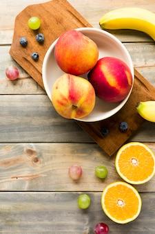 Pesca; mele; uva; mirtilli; banana e arance divise a metà sulla scrivania in legno