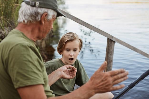 Pesca riuscita, papà che parla di pesci grossi da catturare durante il fine settimana estivo, pesca a mosca con uomo maturo, pescatore con nipote, figlio che guarda padre con bocca aperta ed espressione facciale stupita