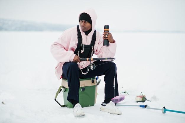 Pescatore afroamericano con la canna da pesca e il thermos. pesca invernale.