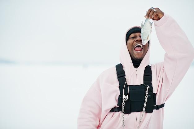 Pescatore afroamericano con pesce congelato fresco a portata di mano. pesca invernale.